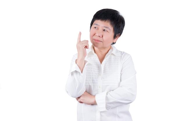 Mulher asiática de meia-idade com camisa branca apontando o dedo e pensando isolado no fundo branco