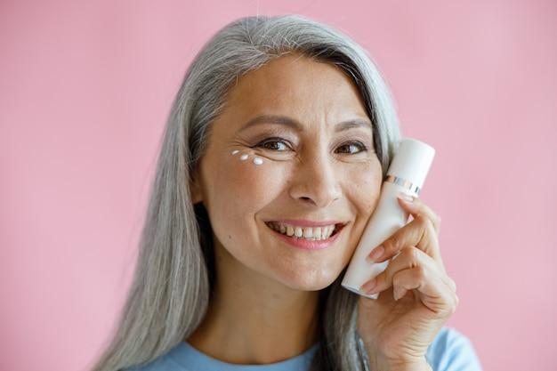 Mulher asiática de meia idade com gotas de creme sob o olho sorridente segura a garrafa perto do rosto no fundo rosa em estúdio. estilo de vida de beleza madura