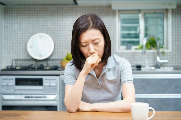 Mulher asiática de meia-idade com um olhar cansado na sala