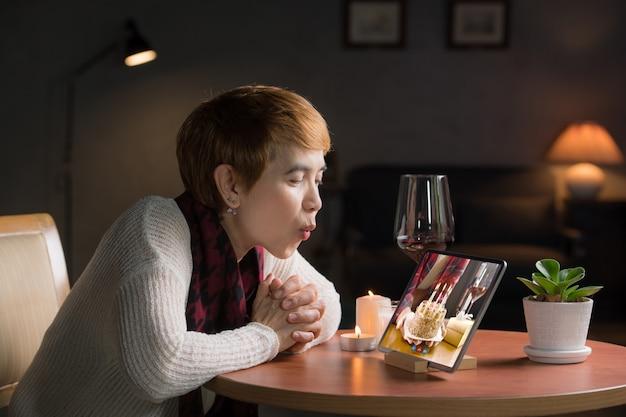 Mulher asiática de meia-idade comemorando aniversário virtual por videochamada em casa durante o distanciamento social