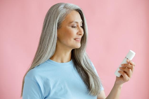 Mulher asiática de meia idade feliz parece um frasco de produto cosmético em fundo rosa