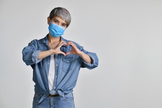 Mulher asiática de meia idade feliz usando máscara cirúrgica para vírus corona e sorrindo apaixonada, mostrando o símbolo e a forma do coração com as mãos isoladas no fundo branco