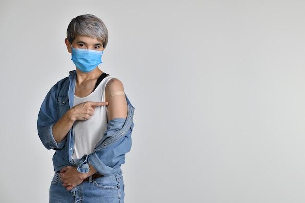 Mulher asiática de meia-idade feliz vacinada, apontando o dedo para a bandagem adesiva em seu braço após injeção antiviral de coronavírus isolada no fundo branco