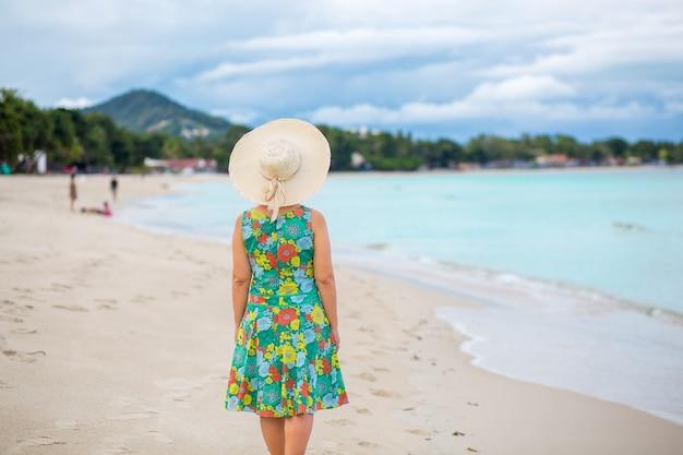 Mulher asiática de meia idade relaxando na praia de chaweng em koh samui, tailândia.