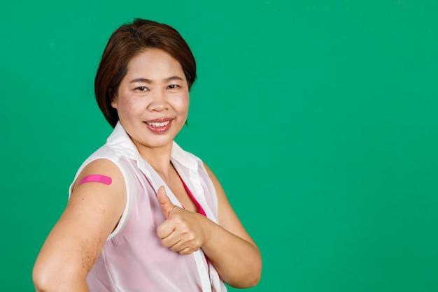 Mulher asiática de meia idade sorrindo e erguendo os polegares, o braço com curativo mostrando que foi vacinada contra o vírus covid 19 em fundo verde. conceito para vacinação contra covid 19.