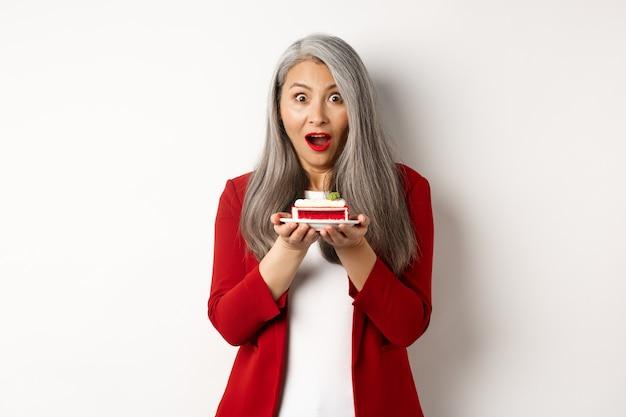 Mulher asiática de meia-idade surpresa, segurando um pedaço de bolo saboroso, parecendo espantada com a câmera, em pé sobre um fundo branco.