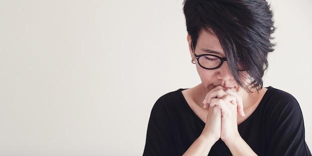 Mulher asiática de meia-idade usa óculos orando, conceito de esperança