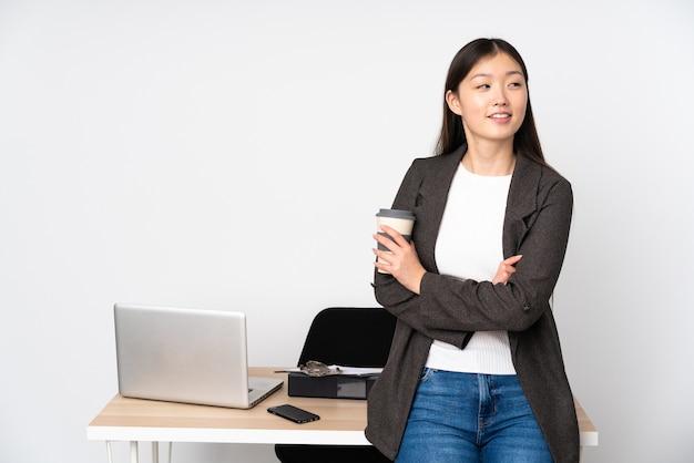 Mulher asiática de negócios em seu local de trabalho isolada no fundo branco com os braços cruzados e feliz