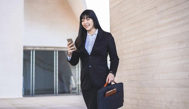 Mulher asiática de negócios fora do prédio usando o aplicativo de smartphone - jovem trabalhadora vai trabalhar - tecnologia, empresário e conceito de emprego - foco no rosto
