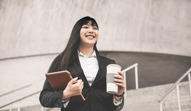 Mulher asiática de negócios indo para o trabalho - feliz empresário feminino fora do escritório antes de uma inicialização bebendo café - tecnologia, empresário e conceito de trabalho - foco em seu rosto