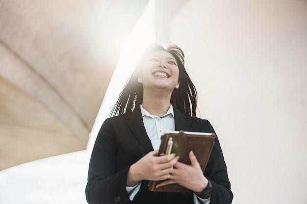 Mulher asiática de negócios indo para o trabalho - feliz empresário feminino fora do escritório após uma inicialização - tecnologia, empresário e conceito de trabalho - foco em seu rosto