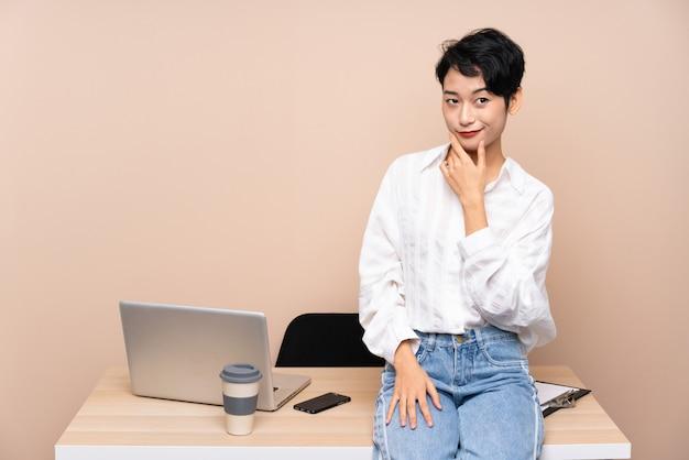 Mulher asiática de negócios jovem em seu local de trabalho, pensando em uma idéia