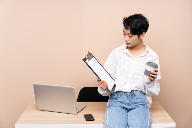 Mulher asiática de negócios jovem em seu local de trabalho