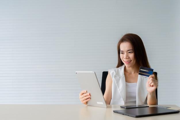 Mulher asiática de negócios jovem segurando o cartão de crédito e usando o tablet