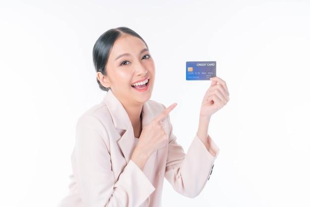 Mulher asiática de negócios mostrando cartão de crédito para compras on-line isoladas no fundo branco, pagando com cartão de crédito, compras on-line, conceito de telemarketing de comércio eletrônico
