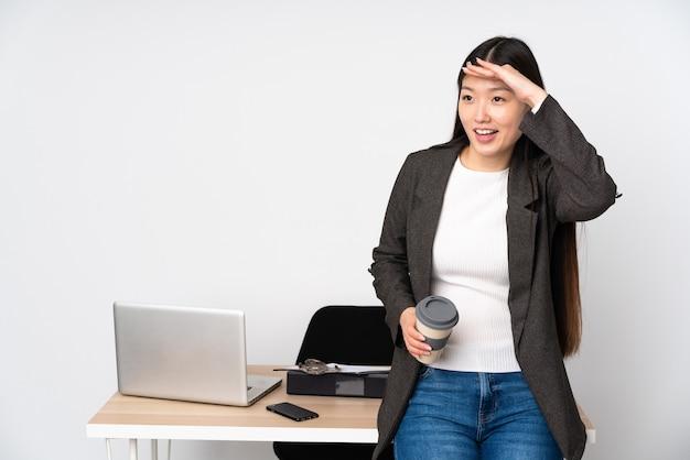 Mulher asiática de negócios no local de trabalho, isolada no fundo branco, olhando para longe com a mão para olhar algo