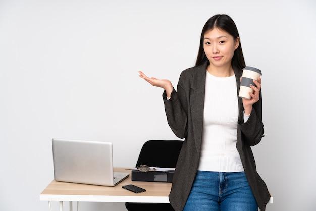 Mulher asiática de negócios no local de trabalho, isolada no fundo branco, tendo dúvidas ao levantar as mãos