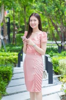 Mulher asiática de negócios profissional com cabelo comprido sorrindo no jardim