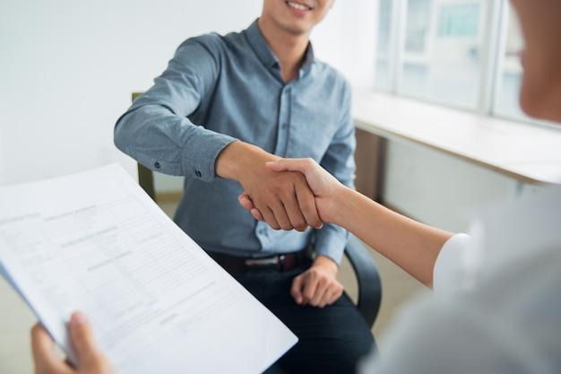 Mulher asiática de negócios que agitam parceiros mão