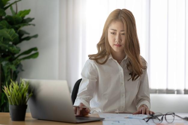 Mulher asiática de negócios usando calculadora para trabalhar com relatório financeiro. ela está trabalhando com um laptop.