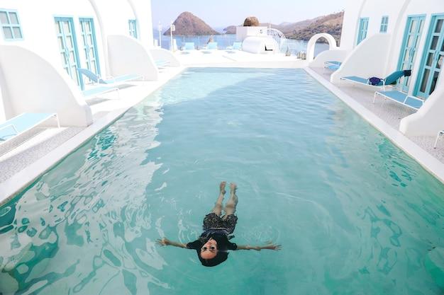 Mulher asiática de óculos escuros flutuando na piscina aproveitando as férias