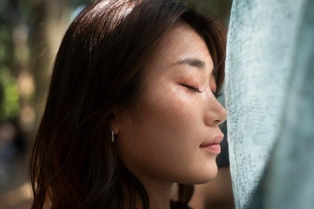 Mulher asiática de olhos fechados