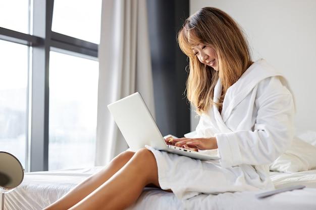 Mulher asiática de roupão sentada digitando no laptop, conversando com alguém ou navegando na internet, fins de semana em casa