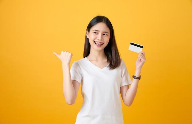 Mulher asiática de sorriso atrativa que guarda o pagamento com cartão de crédito no fundo amarelo com espaço da cópia.