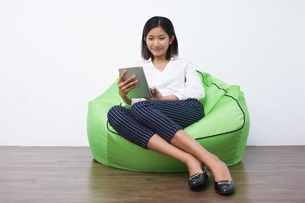 Mulher asiática de sorriso com tabuleta sentado no pufe