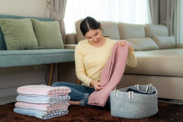 Mulher asiática de sorriso que guarda a roupa dobrada limpa em casa. bela moça sentada no chão com sofá. lavanderia e conceito doméstico. vista frontal.