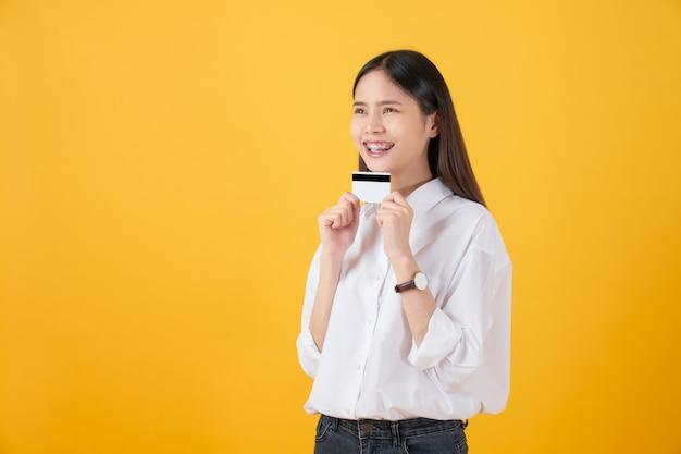 Mulher asiática de sorriso que guarda o pagamento com cartão de crédito no fundo amarelo com espaço da cópia.