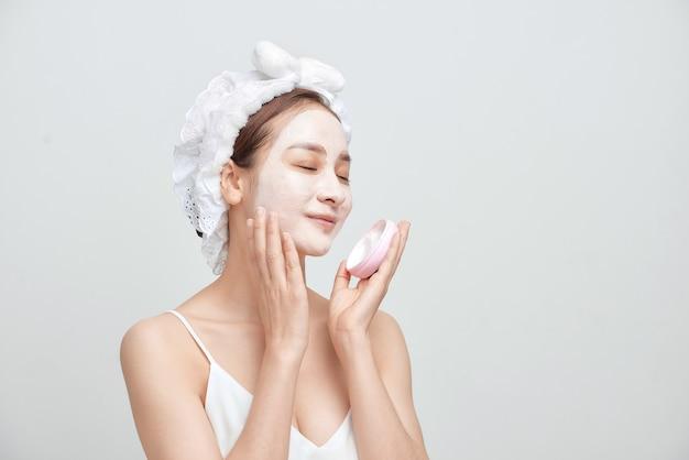 Mulher asiática de spa aplicando máscara de argila facial. conceito de beleza do spa.