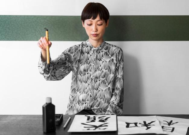 Mulher asiática de tiro médio segurando escova