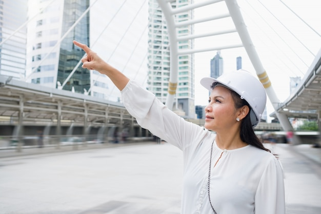Mulher asiática de trabalho usando um capacete está de pé e apontando para a frente.