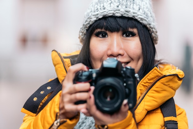 Mulher asiática de turista usando a câmera em uma rua europeia. conceito de turismo.