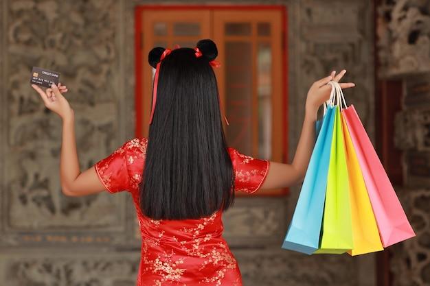 Mulher asiática de vista traseira em um vestido chinês vermelho tradicional cheongsam qipao com um gesto de mostrar o cartão de crédito e segurar sacolas de compras com o fundo da parede antiga (conceito de compra do ano novo chinês)