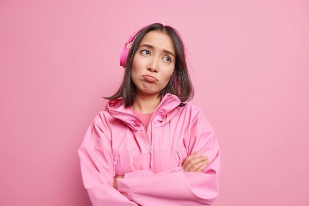 Mulher asiática decepcionada e frustrada com expressão de tristeza sombria mantém os braços cruzados, concentrada, pensativa, longe de ouvir música com fones de ouvido sem fio usa jaqueta isolada na parede rosa