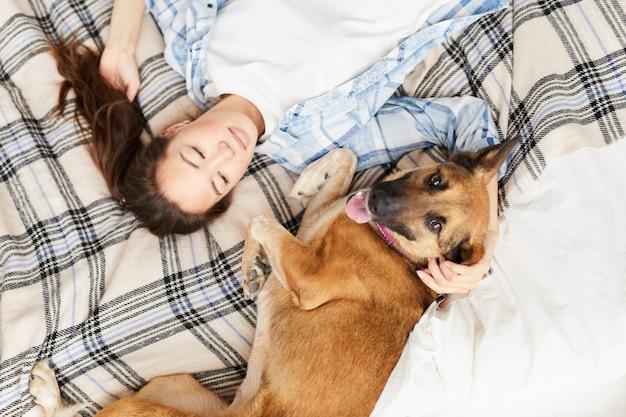 Mulher asiática, deitada na cama com cachorro