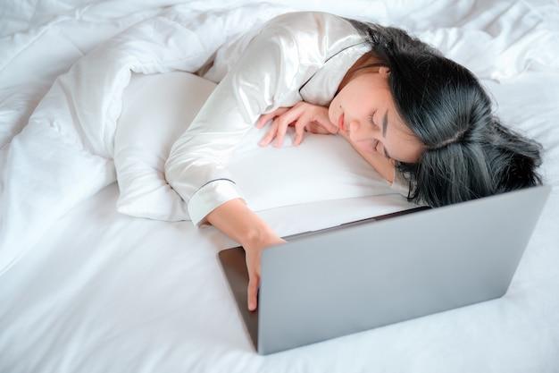 Mulher asiática deitada na cama durante o dia. ela é preguiçosa e dorme depois de trabalhar em um laptop em uma cama branca. ela está cansada de trabalhar na cama tire uma soneca enquanto trabalha