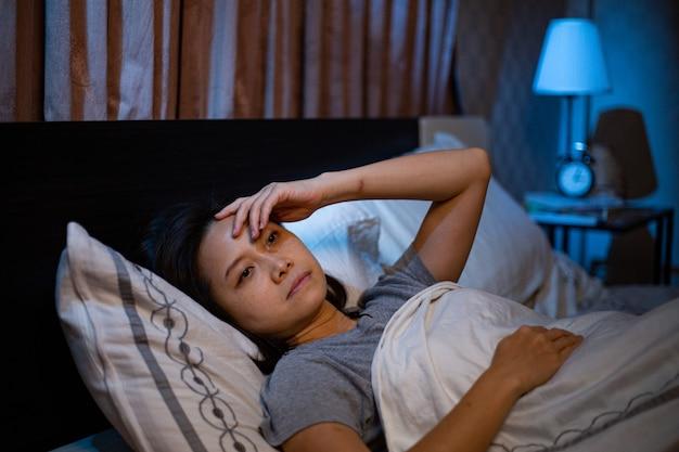 Mulher asiática deprimida não consegue dormir na cama. síndrome da insônia sem dormir após infeliz e preocupada com seu estilo de vida. adulto sente tristeza. emoção triste.