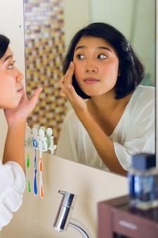 Mulher asiática, descobrindo uma espinha no rosto