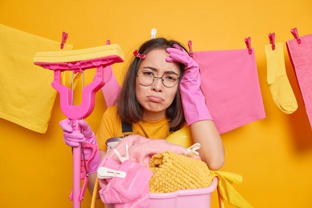 Mulher asiática descontente olha com tristeza para a câmera. expressão de rosto frustrada lava roupa e faz limpeza em casa usa luvas de borracha em volta de óculos posa contra roupas lavadas penduradas no varal