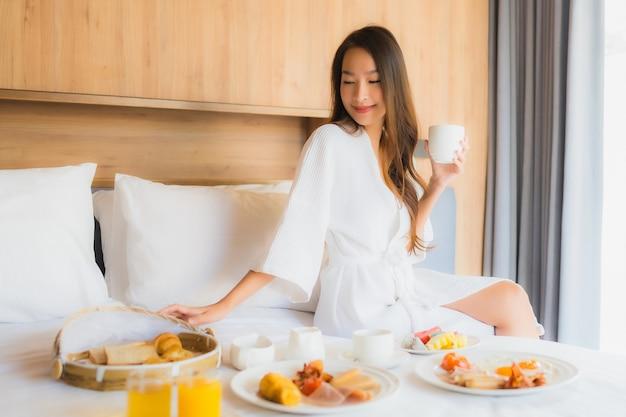 Mulher asiática, desfrutando com café da manhã na cama