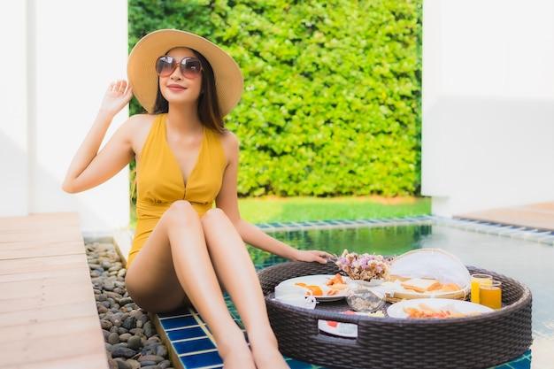 Mulher asiática, desfrutando com café da manhã na piscina