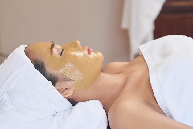 Mulher asiática, desfrutando de procedimento de skincare