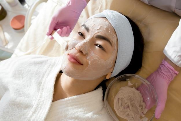 Mulher asiática, desfrutando de tratamento de beleza em spa