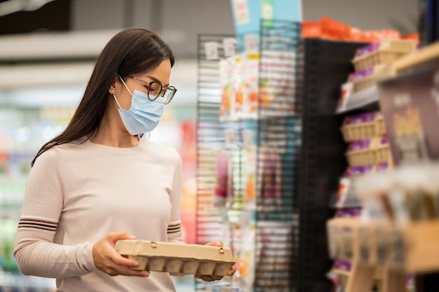 Mulher asiática, desgastar, máscara facial, compras, em, supermercado, durante, vírus corona