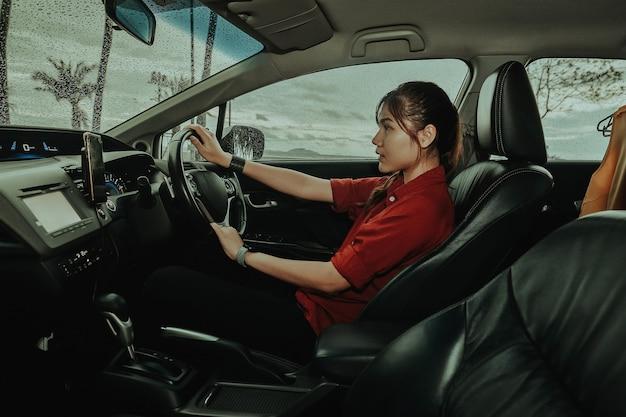 Mulher asiática dirigindo carro atraente garota sentada em um automóvel chovendo ao ar livre