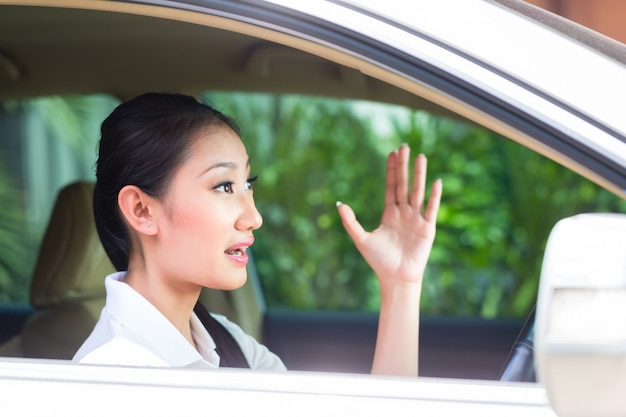 Mulher asiática dirigindo carro novo