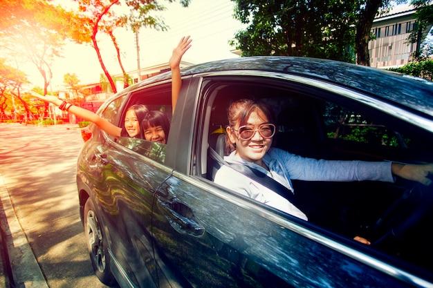 Mulher asiática, dirigindo o carro com o adolescente de felicidade no banco do passageiro